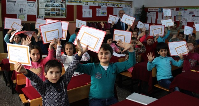 Children at a school in the northern Turkish province of Tokat's Erbaa district show their report cards.