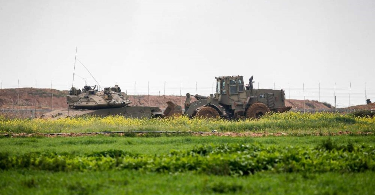 An Israeli Merkava battle tank and an earth mover along the Israel-Gaza border east of Khan Yunis in the southern Gaza Strip, Feb. 23, 2020. (AFP Photo)