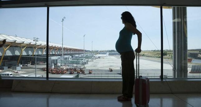 A pregnant woman waits at an airport. (iStock)
