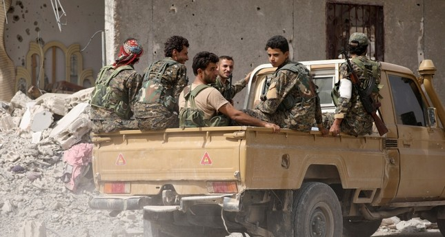 Fighters from the YPG-controlled Syrian Democratic Forces (SDF) sit on the back of a pick-up truck in Raqqa, Syria Sept. 25, 2017. (Reuters Photo)