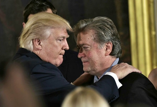 President Donald Trump (L) congratulating Senior Counselor to the President Stephen Bannon during the swearing-in of senior staff on January 22, 2017. AFP Photo