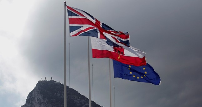 The Union Jack (L), the Gibraltarian flag (C) and the EU flag are seen flying, at the border of Gibraltar with Spain, in front of the Rock in the British overseas territory of Gibraltar, historically claimed by Spain April 3, 2017. (Reuters Photo)