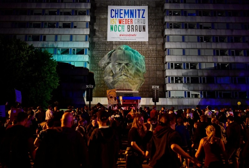 People have a rave in front of the Karl-Marx statute after the