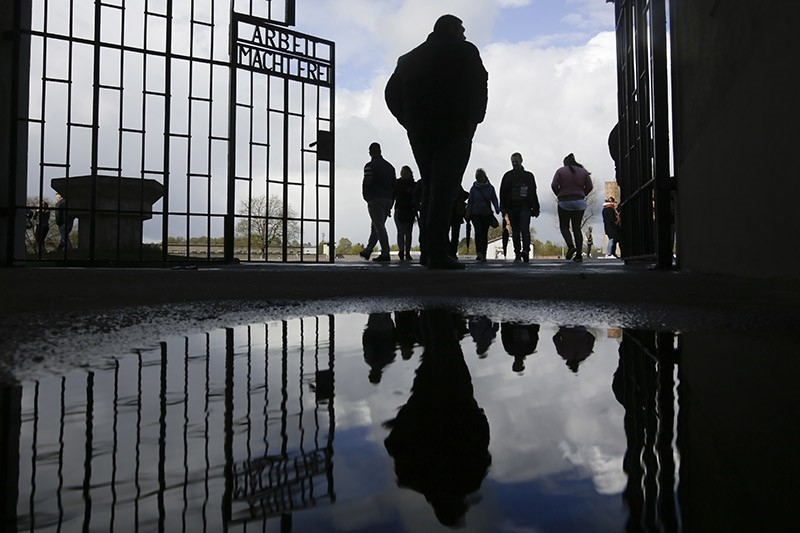 People enter the Sachsenhausen Nazi death camp through the gate with the inscription 'Arbeit macht frei' (work sets you free) in Oranienburg, about 35 kilometer north of Berlin Sunday, April 23, 2017. (AP Photo)
