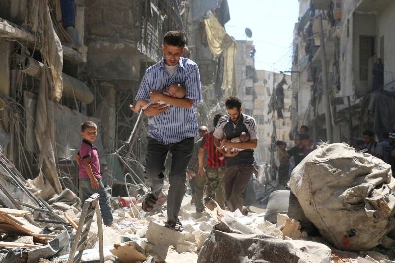 Photo shows Syrian men carrying babies as they make their way through the rubble of destroyed buildings following a reported air strike on Salihin neighborhood of the northern city of Aleppo, Syria, Sept. 11, 2016. (AFP/AP Photo)