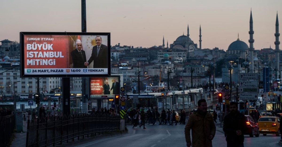 People walk in front of an election billboard depicting President Recep Tayyip Erdou011fan and the Nationalist Movement Party (MHP) leader Devlet Bahu00e7eli of the People's Alliance, ahead of the March 31 local elections, Istanbul, March 22, 2019.