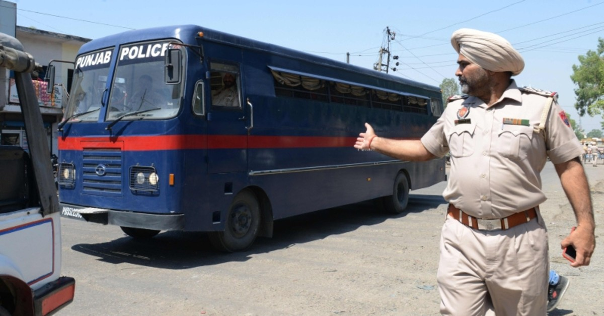Indian Punjab Police personnel escort a police vehicle carrying the seven accused for the rape and murder of an 8-year-old nomadic girl in Kathua in Jammu and Kashmir, at the district court in Pathankot on June 10, 2019. (AFP Photo)