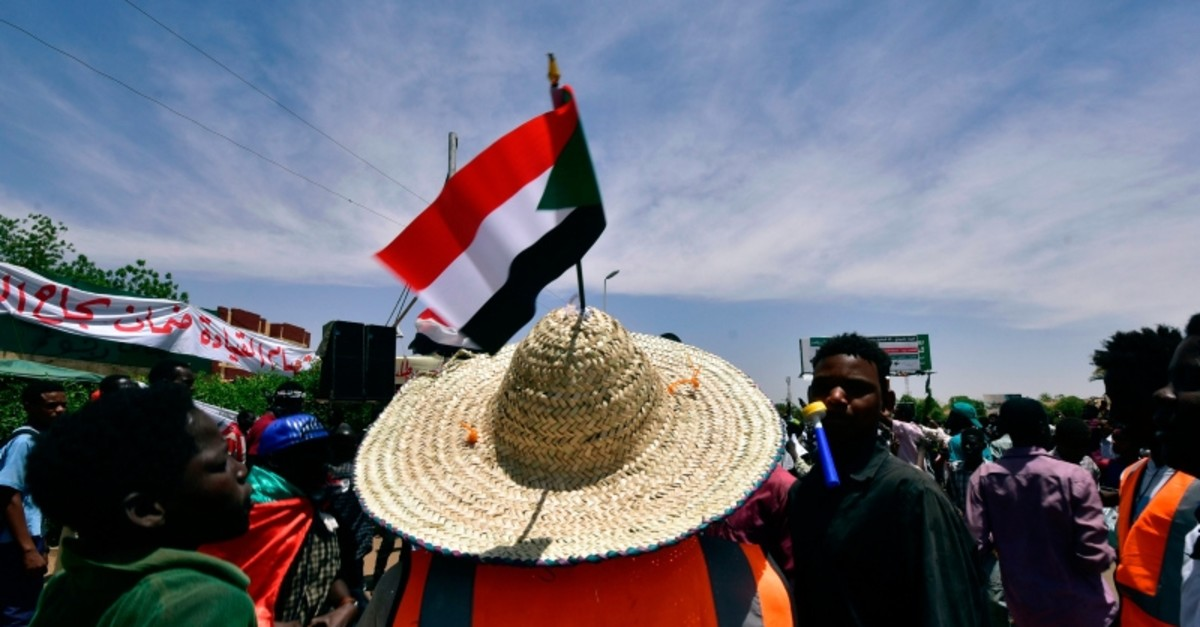 Sudanese demonstrators march with national flags as they gather during a rally demanding a civilian body to lead the transition to democracy, outside the army headquarters in the capital Khartoum, Sudan, Saturday, April 14, 2019. (AFP Photo)