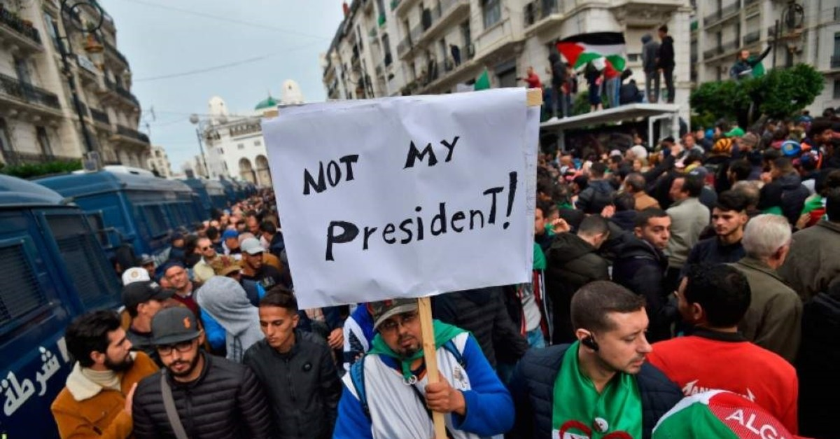 An Algerian protester lifts a placard in the capital Algiers on Dec. 13, 2019, as he takes part in a demonstration to reject the results of the presidential elections. (AFP Photo)