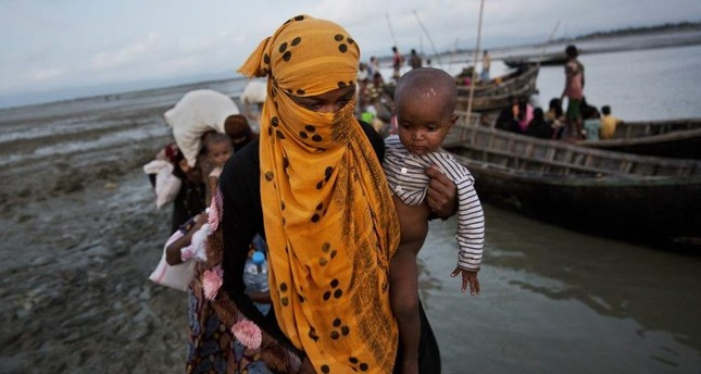 In this Sept. 21, 2017 photo, a Rohingya woman carries a child after crossing a stream on a small boat near Cox's Bazar's Dakhinpara area, Bangladesh. AP Photo