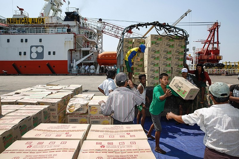 Myanmar workers load boxes of relief aid for Rohingya Muslims delivered by humanitarian aid Malaysian ship Nautical Aliya seen in the background in Yangon's Thilawa port on February 10, 2017. (AFP Photo)