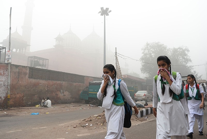 Indian schoolchildren cover their faces as they walk amid heavy smog in New Delhi on November 8, 2017. (AFP Photo)