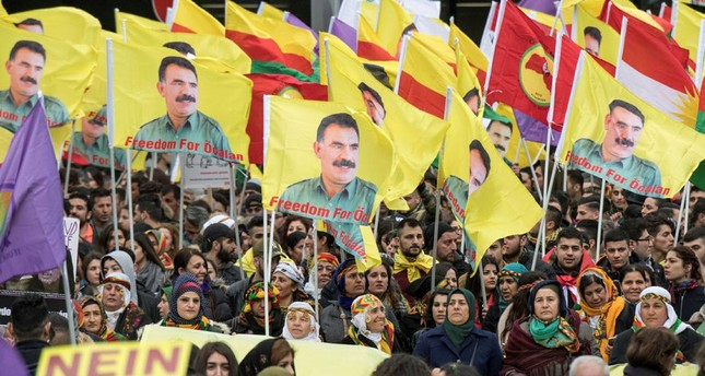 PKK supporters in Germany gather and wave flags with portraits of detained leader Abdullah Öcalan in Frankfurt, Germany, Saturday, March 18, 2017. (DPA via AP)