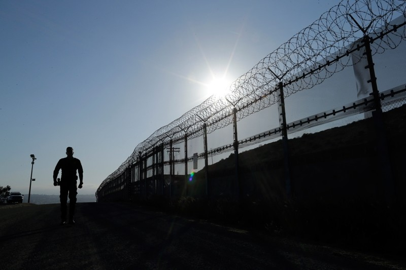 In this June 22, 2016 file photo, a Border Patrol agent walks along a border structure in San Diego, Calif. (AP File Photo)