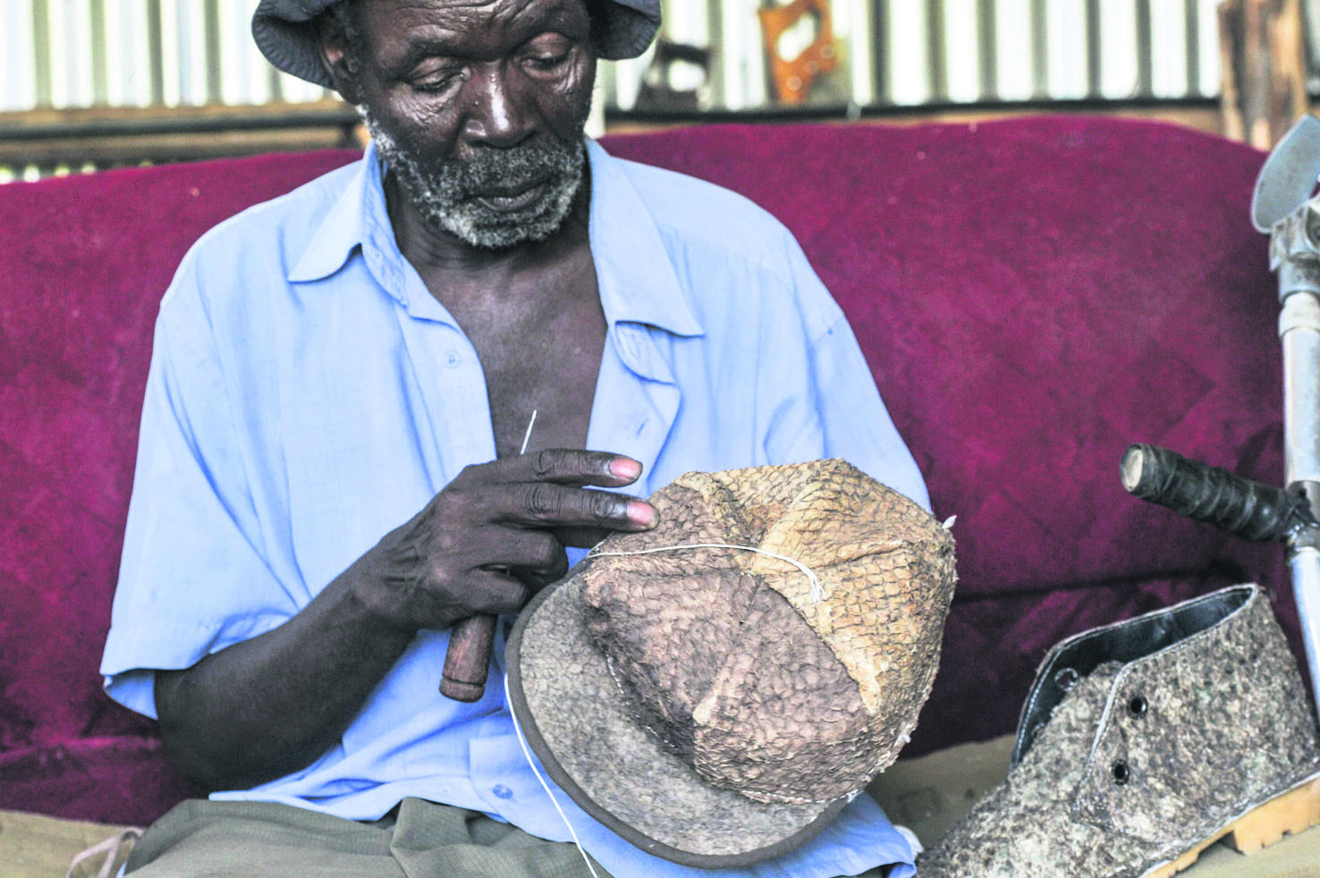 An employee adds some finishing touches to leather hat and shoe made out of tanned fish pelts.