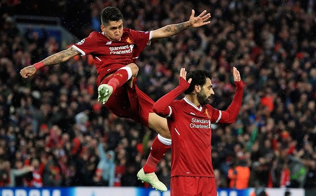Liverpool's Mohamed Salah, right, celebrates scoring his side's second goal of the game with Roberto Firmino against Roma during their Champions League, Semifinal first leg match at Anfield, Liverpool, U.K., April 24, 2018. PA via AP