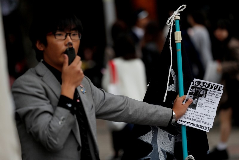 A man speaks on a loudspeaker with leaflets denouncing South Korean boy band BTS outside Tokyo Dome where the band's concert is planned to be held, in Tokyo, Japan, November 13, 2018. (Reuters Photo)
