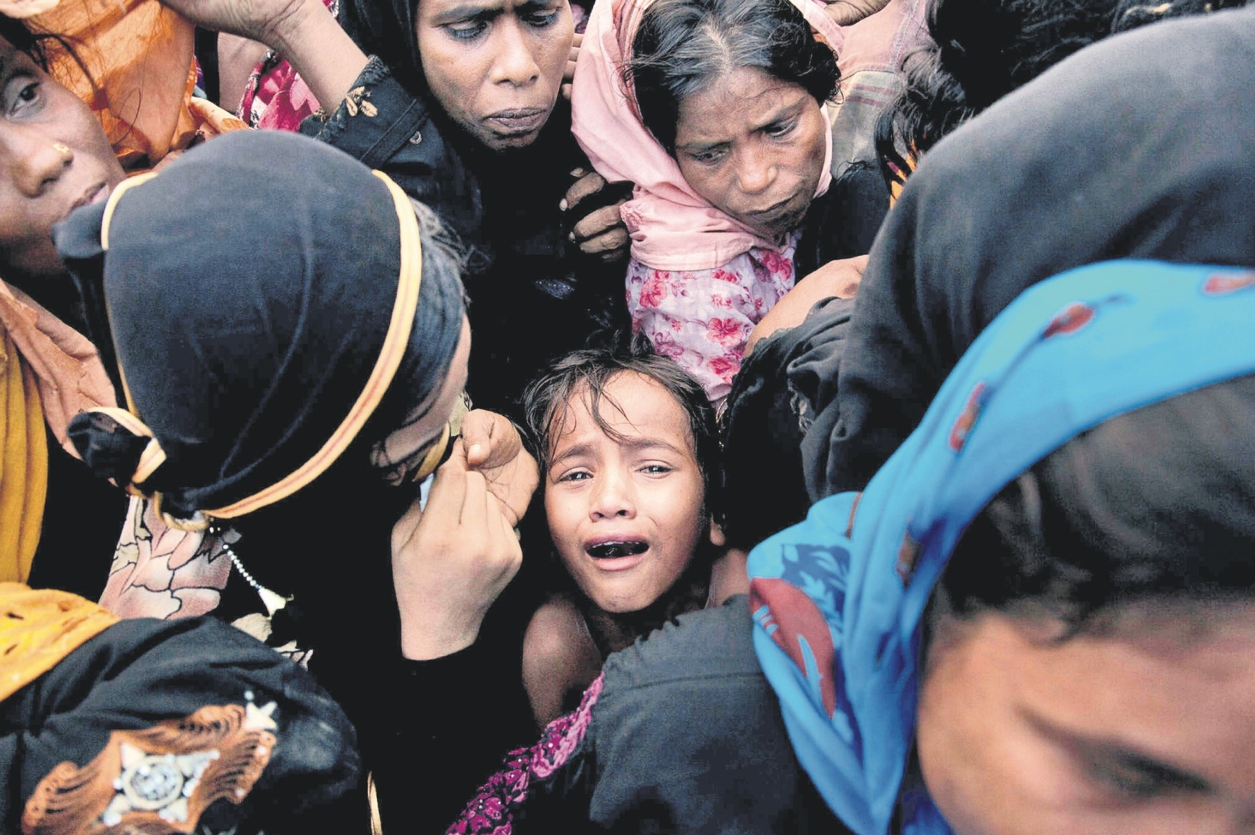 A Rohingya refugee child cries as she stands amid a crowd to receive food being distributed near Balukhali refugee camp, Cox's Bazar, Bangladesh, Sept. 20, 2017.