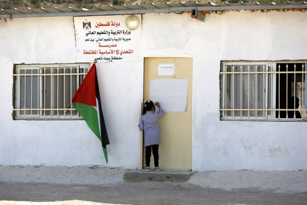 A Palestinian child knocks on the door of a school in the West Bank village of Jeb Deeb, near Bethlehem, Nov. 18.