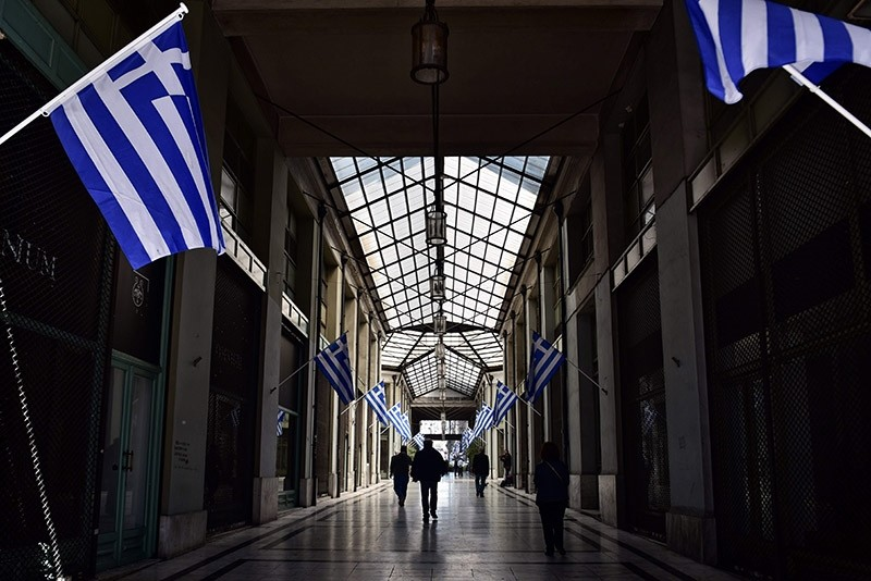 Men walk in a passage adorned with Greek flags in central Athens on March 21, 2017. (AFP Photo)