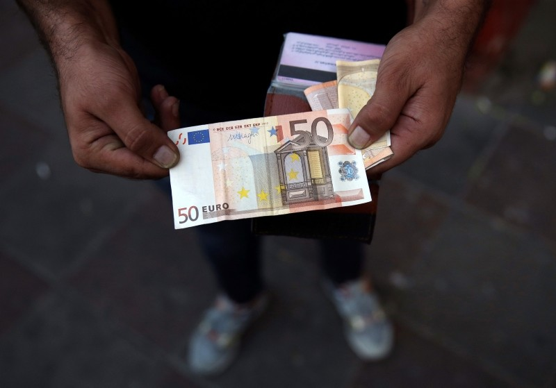 An Iranian street money exchanger holds a 50 euro banknote in downtown Tehran, Iran, Monday, July 30, 2018. (AP Photo)