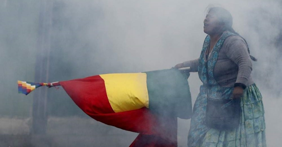 In this Wednesday, Nov. 13, 2019 photo, a supporter of former President Evo Morales holds a Bolivian flag during clashes with police in La Paz, Bolivia. (AP Photo)