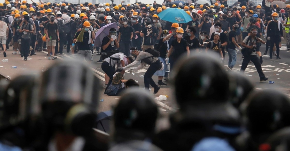 Protesters help a fallen person after clashing with riot police during a massive demonstration outside the Legislative Council in Hong Kong. (AP Photo)