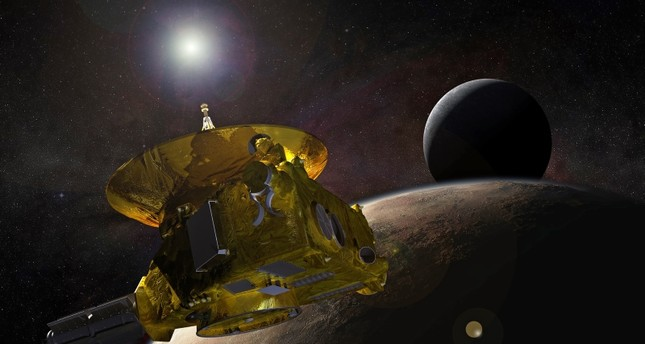 A handout photo made available by NASA shows an artist's concept of the New Horizons spacecraft as it approaches Pluto and its largest moon, Charon, in July 2015. (EPA Photo)