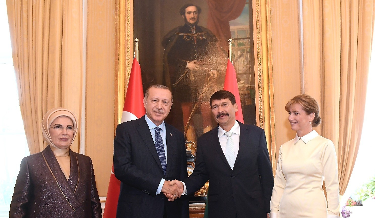 President Recep Tayyip Erdou011fan shakes hands with Hungarian President Janos Ader as their wives Emine Erdou011fan (L) and Anita Herczegh (R) look on during their meeting at the presidential Alexander Palace in Budapest, yesterday.