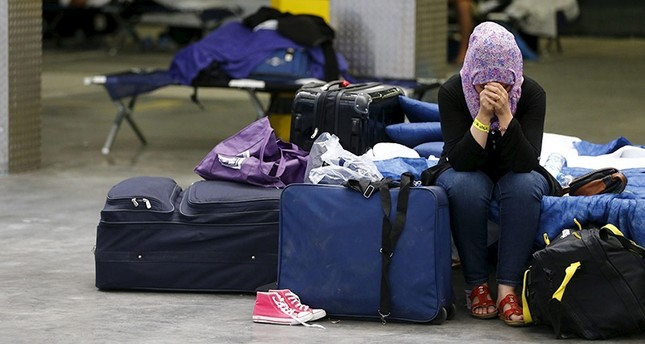 A Syrian woman cries as she sits on a folding bed in a former newspaper printing house used as a refugee registration centre for the German state of Hesse in Neu-Isenburg, on the outskirts of Frankfurt, Germany, September 11, 2015. (Reuters Photo)