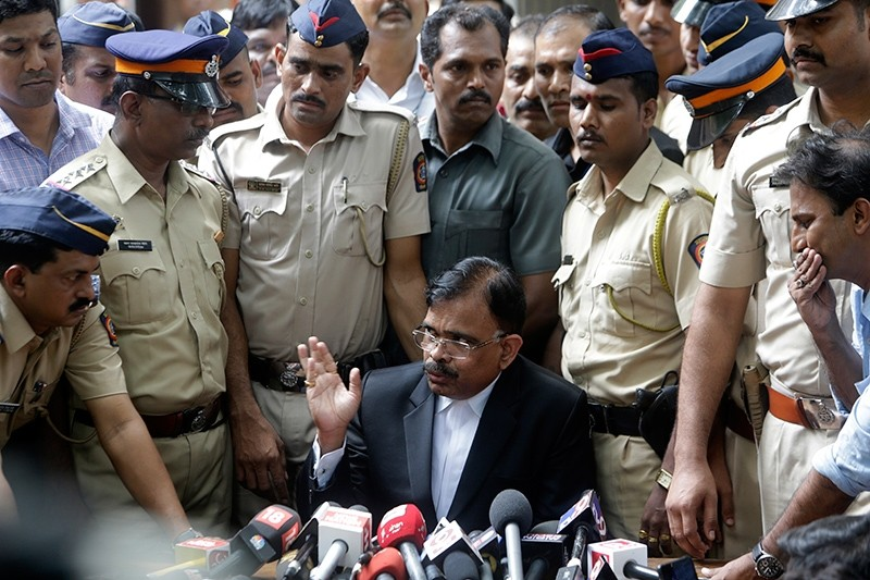 Public Prosecutor D. N. Salvi, seated center, speaks to the media outside the sessions court complex in Mumbai, India, Sept. 7, 2017. (AP Photo)