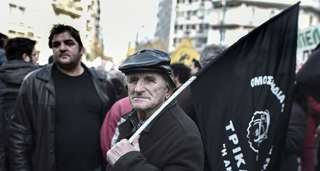 A Greek farmer holds a flag during a protest against new tax hikes and pension reforms that are part of Greece's austerity programme during an anti-austerity demonstration on February 14, 2017 in central Athens. (AFP Photo)