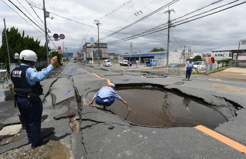 Police check a collapsed road following an earthquake in Takatsuki, north of Osaka prefecture on June 18, 2018. (AFP Photo)