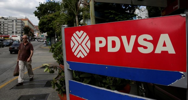 A man walks past the corporate logo of the state oil company PDVSA at a gas station in Caracas, Venezuela December 1, 2017. Reuters Photo