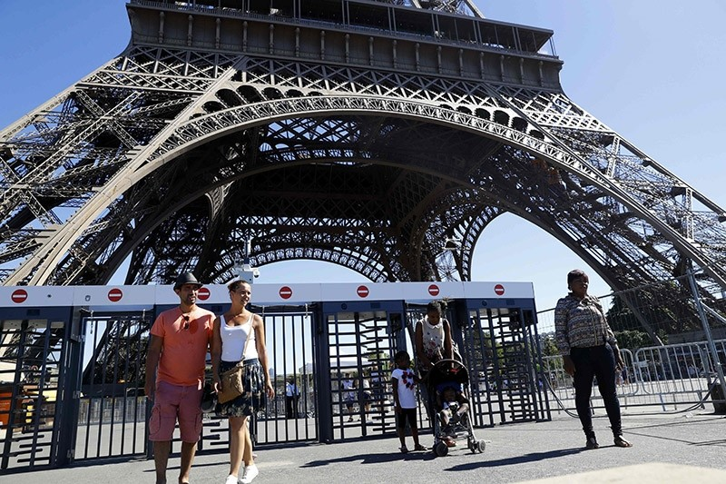 This file photo taken on August 24, 2016 in Paris shows people walking past security gates at the Eiffel Tower. (AFP Photo)