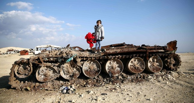 Rawan, an 11-year-old Syrian girl poses on a destroyed tank with her stuffed bear near the village of Yazi Bagh, about 6 kilometers from the Bab al-Salamah border crossing between Syria and Turkey in Aleppo province, Feb. 19, 2019.