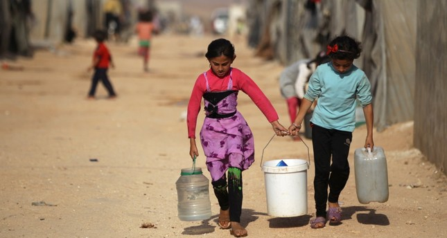 Internally displaced Syrian girls carrying water containers in Jrzinaz camp, south Idlib, Syria, June 21, 2016.