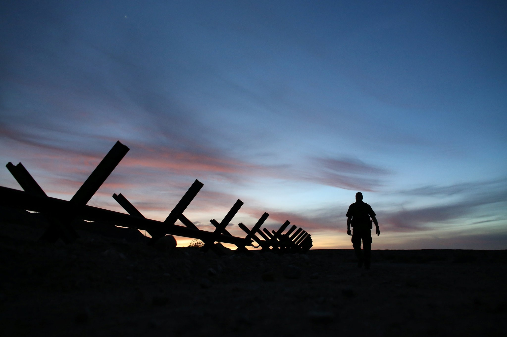 U.S. border patrol agent Alessio Faccin walks along the border fence separating Mexico from the United States near Calexico, California, U.S. February 8, 2017. picture taken February 8, 2017. (REUTERS Photo)