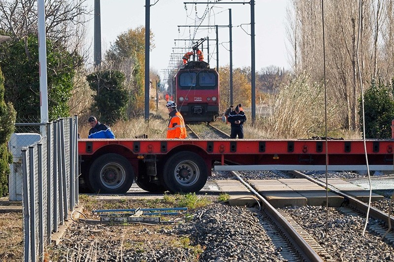 Gendarmes and employees of the National society of French railways (SNCF) investigate at a level crossing in Millas, on December 17, 2017. (AFP Photo)