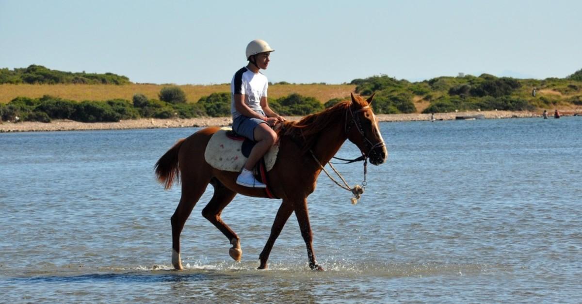 A tourist enjoys a horseback safari in Aydu0131n's resort town of Didim.