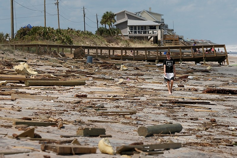 A boy walks amongst debris on the beach after Hurricane Irma passed the area in Ponte Vedra Beach, Florida, U.S., September 12, 2017. (Reuters Photo)
