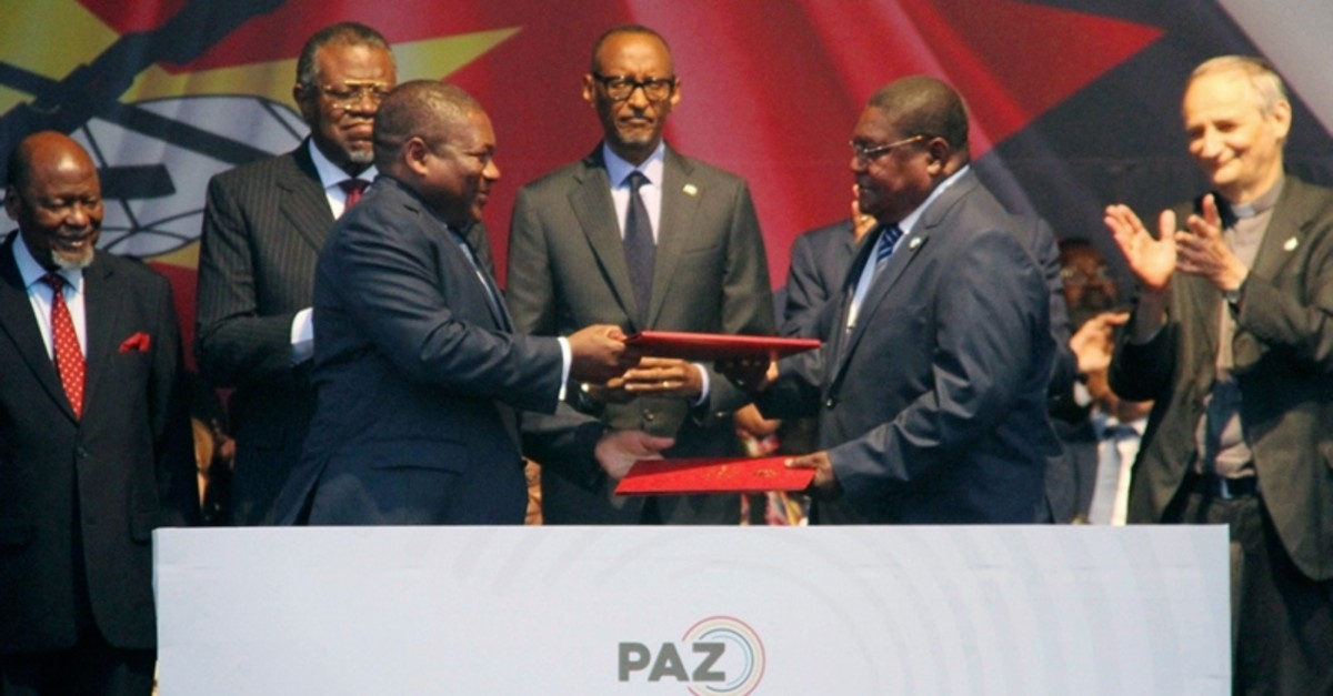 Mozambican President Filipe Nyusi, left, and Renamo leader Ossufo Momade exchange documents, at a signing agreement in Maputo, Mozambique, Tuesday, Aug. 6, 2019. (AP Photo)