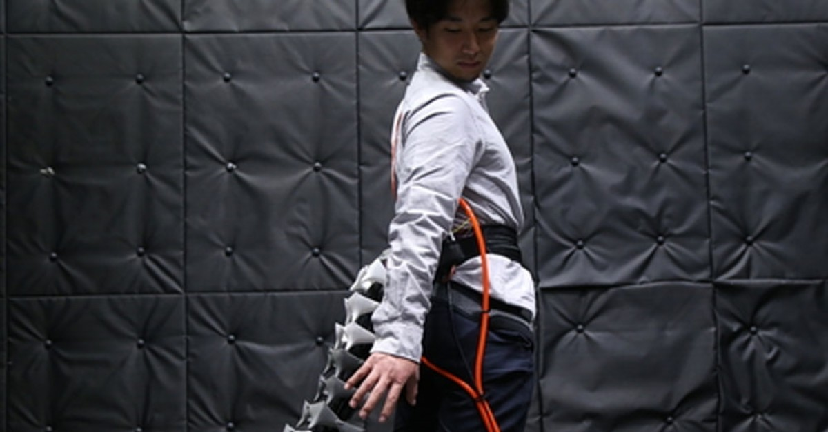 A man tries the robot tail which aims to offer balance to the elderly.