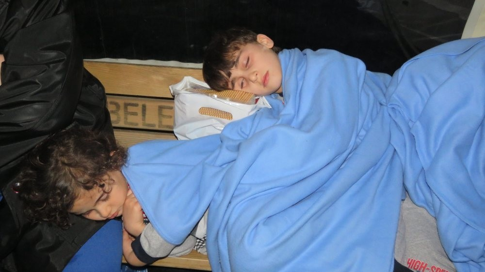 Two children rescued from a migrant boat that sank off the Turkish coast sleep on a bench at the Ku00fcu00e7u00fckkuyu port they were taken to in February.