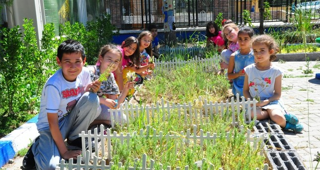 Children pose with the herbs they grew.