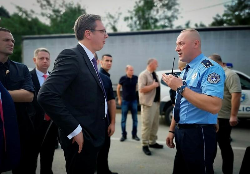 A Kosovo police officer speaks to Serbia's president Aleksandar Vucic, left, to say he cannot continue his trip to the village of Banje due to roadblocks, in Zubin Potok, Kosovo, Sunday, Sept. 9, 2018. (Serbian Presidency via AP)
