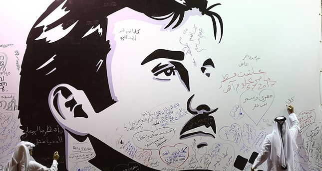 This file photo taken on July 6, 2017 in the Qatari capital Doha shows a man writing comments on a wall bearing portrait of Emir Sheikh Tamim bin Hamad Al Thani, which became symbol of resistance during the month-long Gulf crisis. (AFP Photo)