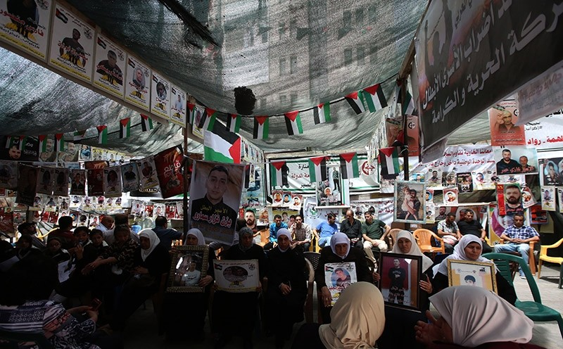 Palestinians sit among pictures of men held in Israeli jail during a protest in solidarity with Palestinian prisoners on hunger strike in Israeli jails, in the West Bank city of Nablus. EPA Photo