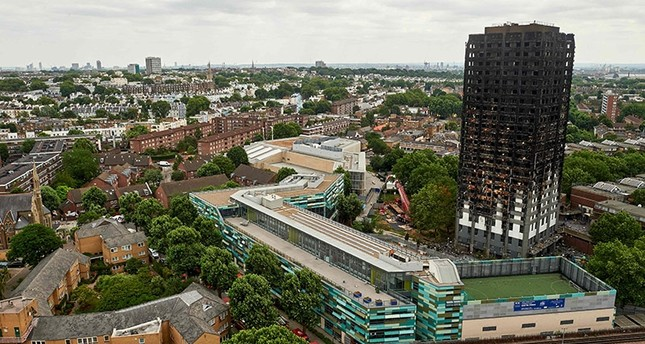 The unburned lower floors with untouched cladding still in place are pictured, with the burnt out upper floors above, at the remains of the Grenfell Tower block in north Kensington, west London on June 22, 2017. (AFP Photo)