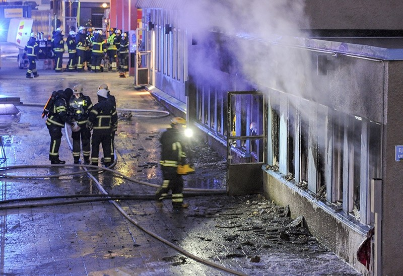 Firemen work outside a still smoking cellar mosque in Eskilstuna, Sweden, Thursday, Dec. 25, 2014. (AP Photo)